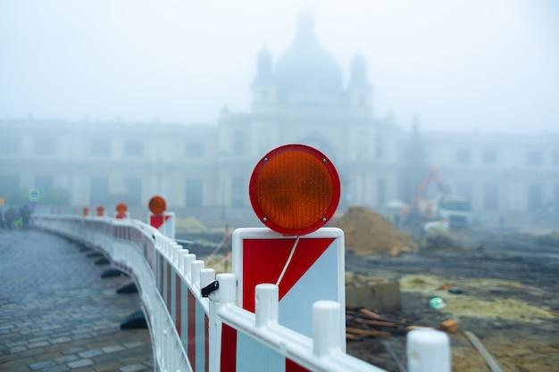 Obras rodoviárias em frente a um edifício histórico no meio do nevoeiro. vedação com sinal luminoso.