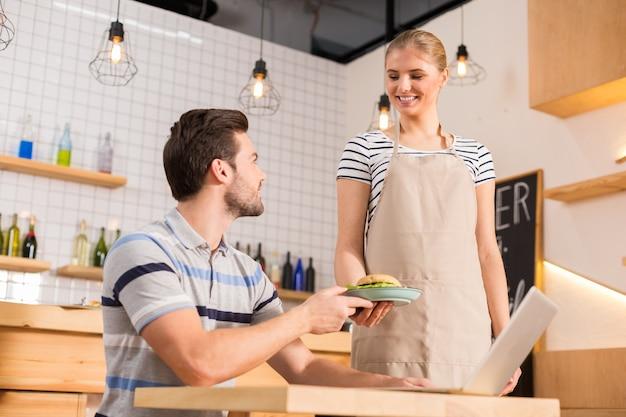 Obrigada. homem feliz e simpático, sentado à mesa e pegando um prato com hambúrguer, enquanto visita um café