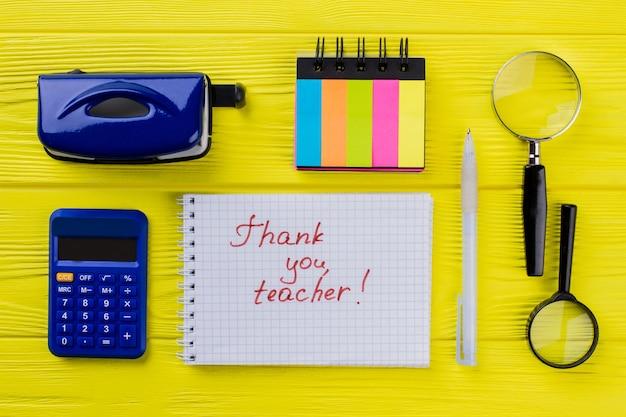 Obrigada professora. conceito do dia do professor plana leigos. calculadora, bloco de notas, caneta e grampeador.