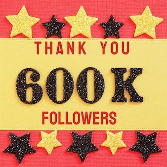 Obrigado 600k, 600000 seguidores. mensagem com números brilhantes pretos em vermelho e dourado