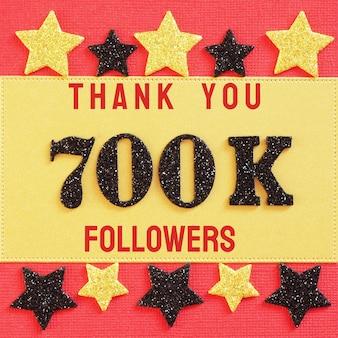 Obrigado 700k, 700000 seguidores. mensagem com números brilhantes pretos em vermelho e dourado