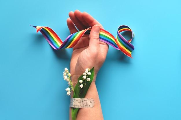 Obrigado médicos e enfermeiros! fita de arco-íris na mão de uma mulher madura com buquê de flores e grama de camomila anexado com remendo de ajuda médica