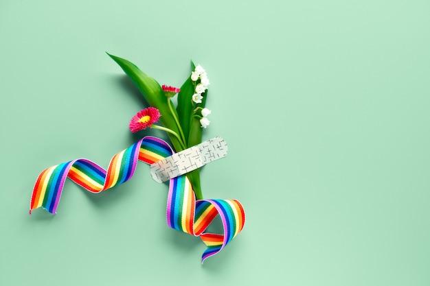 Obrigado médicos e enfermeiros! fita do arco-íris na mão da mulher madura com buquê de flores e grama de camomila anexado com remendo de ajuda médica.