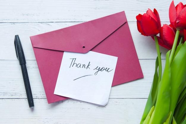Obrigado mensagem e envelope na mesa de madeira