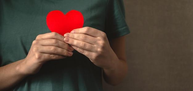 Obrigado meu deus. senhora segurando coração vermelho perto do corpo. expressando profunda gratidão, impressionado com a foto do conceito de boa ação