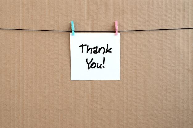 Obrigado! nota está escrito em um adesivo branco que trava com um pregador