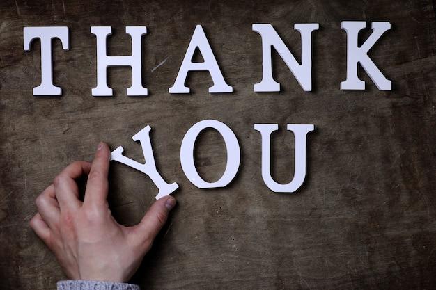 Obrigado palavra de letras brancas de madeira na mesa e nas mãos