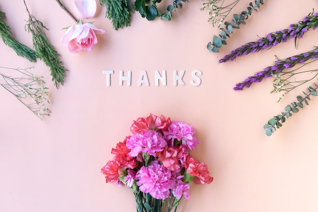 Obrigado palavra de madeira com cravos de flores frescas em fundo rosa suave creme