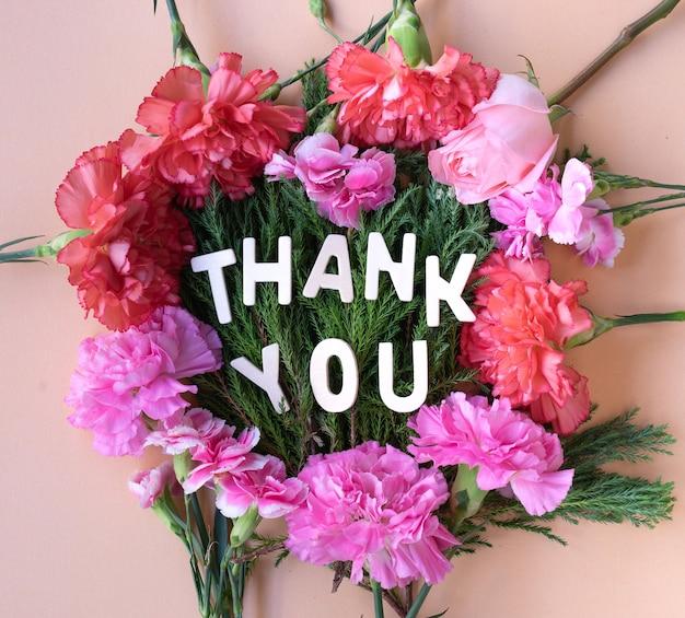 Obrigado palavra de madeira na moldura de cravos de flores frescas em fundo rosa suave creme
