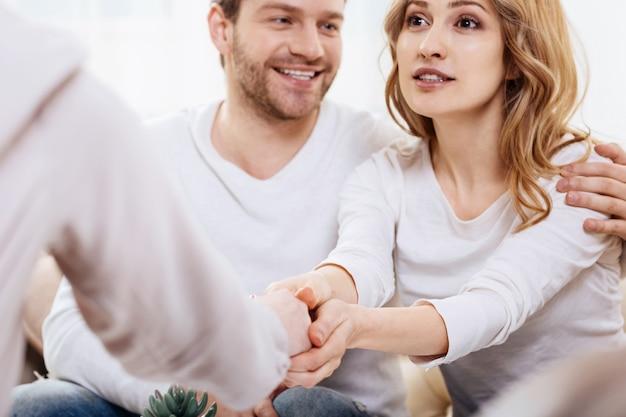 Obrigado pela ajuda. mulher bonita e encantada segurando a mão de seu psicólogo e expressando sua gratidão enquanto está sentado com seu marido em frente a ela