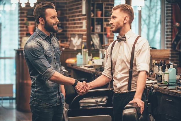 Obrigado pelo corte de cabelo de qualidade! barber e seu cliente apertando as mãos com um sorriso