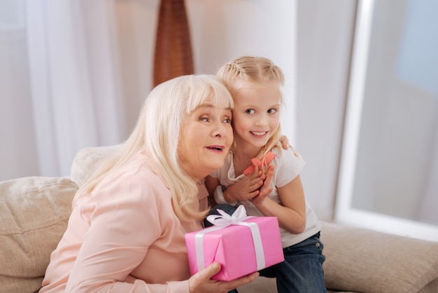 Obrigado por um presente. mulher idosa e simpática encantada sorrindo e segurando uma caixa de presente enquanto abraça a neta