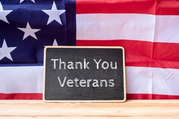 Obrigado veteranos texto escrito na lousa com bandeira dos estados unidos