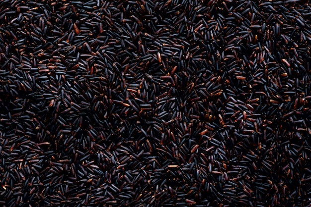 Obscuridade crua - vermelho, arroz roxo traseiro, textura. padrão de riceberry. ingrediente alimentar. vista superior, conceito de estilo de vida saudável.