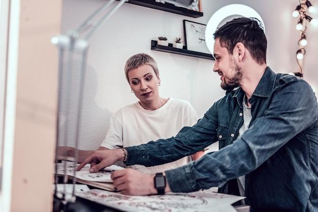 Observando projetos. mestre da tatuagem feminina se surpreendendo com a escolha de seu cliente enquanto ele apontava na página