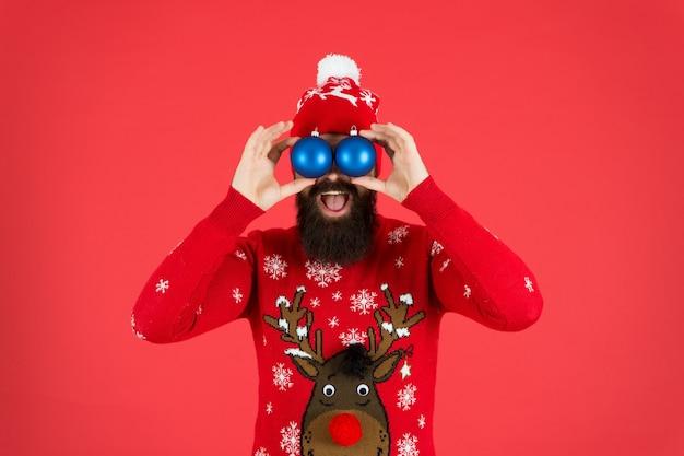Observando você. decorações festivas. atividades de inverno essenciais para as famílias. hipster barbudo homem usar chapéu de suéter de inverno segurar bolas fundo vermelho. conceito de ano novo. festa de natal. roupa de inverno.