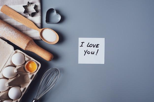 Observe eu te amo. ingredientes para fazer biscoitos caseiros em um fundo cinza.