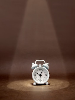 Observe o despertador em um feixe de luz em um fundo escuro. a ideia de um negócio, um conceito financeiro e a economia de tempo e dinheiro. formato vertical