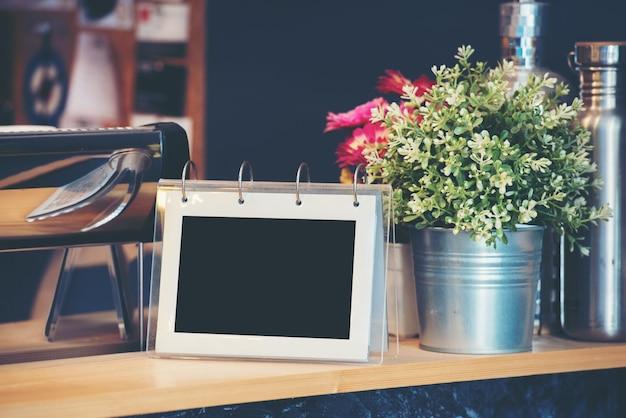 Observe o quadro sobre uma mesa de madeira em uma cafeteria.