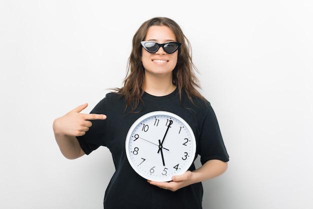 Observe o tempo. não perca a oferta, diz uma garota segurando um relógio de parede.