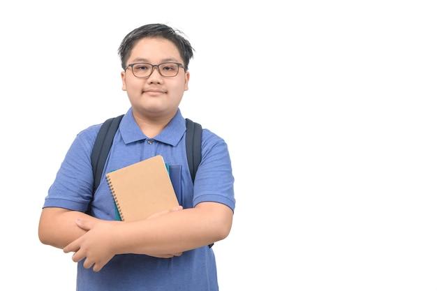 Obses menino estudante vestindo uma camisa polo azul usando óculos segurando um caderno isolado no fundo branco, volta às aulas e conceito de educação