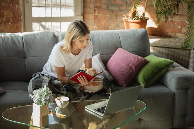 Obtendo tarefas. mulher caucasiana, freelancer durante o trabalho em home office durante a quarentena. jovem empresária em casa, auto-isolada. usando gadgets. trabalho remoto, prevenção de disseminação de coronavírus.