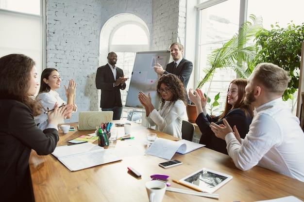 Obtenha o alvo. grupo de jovens profissionais de negócios em uma reunião. diversos grupos de colegas de trabalho discutem novas decisões, planos, resultados e estratégias. criatividade, local de trabalho, negócios, finanças, trabalho em equipe.