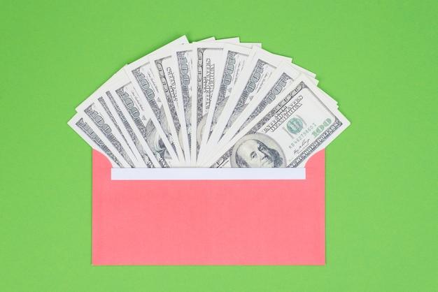 Obter dinheiro de depósito de crédito do conceito de banco. acima, close-up, veja a foto de um envelope vermelho cheio de dinheiro isolado sobre um fundo verde brilhante