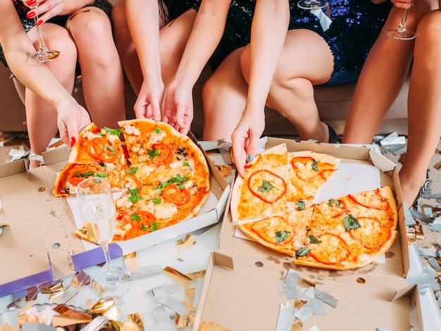Ocasião especial. foto recortada de senhoras em minissaias sentadas, comendo pizza, bebendo vinho espumante.