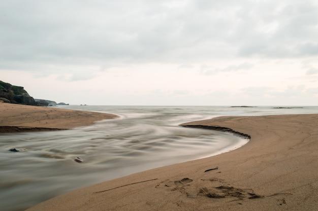 Oceano atlântico. em primeiro plano, um riacho deságua no mar