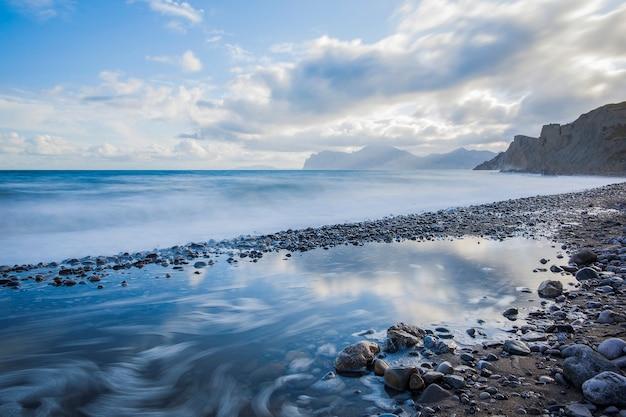 Oceano calmo coberto de névoa, céu brilhante com nuvens. montanhas distantes à direita