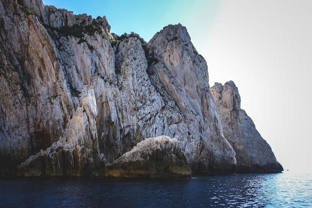 Oceano cercado por penhascos rochosos brilhando sob o céu azul
