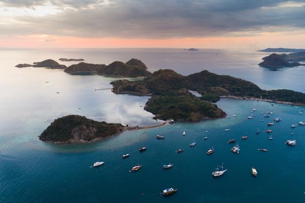 Oceano oceânico com muitos barcos e montanhas situados em indonésia.