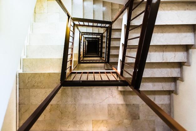 Oco das escadas de um edifício que dá uma sensação de vertigem.