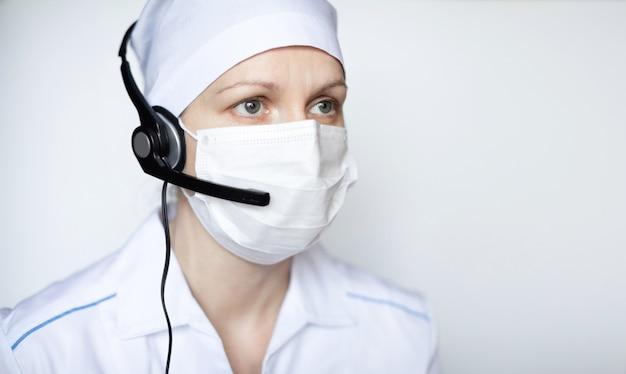 Octor do retrato nos auriculares que desgasta a máscara protetora no fundo branco, com área em branco do copyspace para o texto.