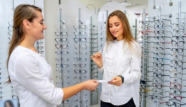 Oculista está ajudando uma cliente a escolher óculos em ótica