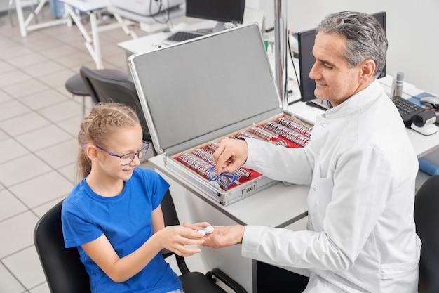 Oculista masculina dando lente e óculos para pequeno paciente
