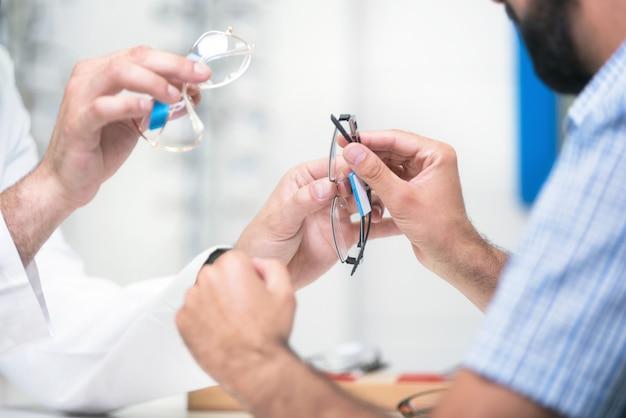 Oculista oferecendo óculos ao cliente para testar e tentar