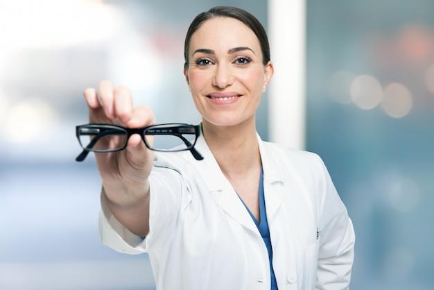 Oculista sorridente, mostrando os óculos