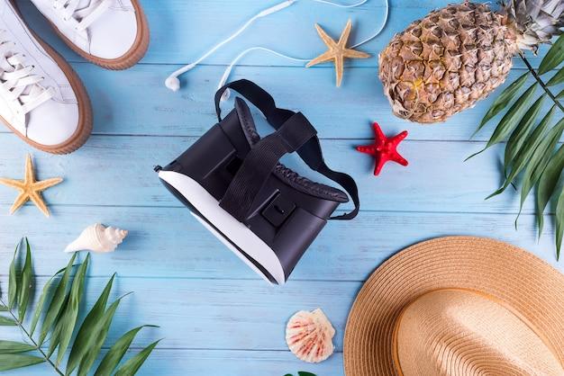 Óculos 3d com folha de palmeira, sapatos, chapéu e abacaxi em um fundo azul de madeira. conceito de viajar em realidade virtual