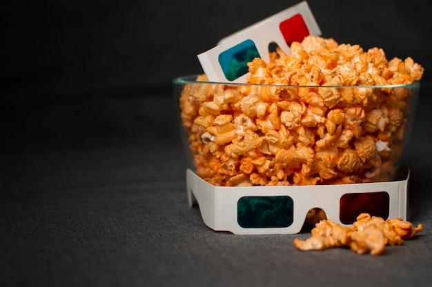 Óculos 3d e pipoca de queijo mentem em um prato de vidro em uma cama cinza