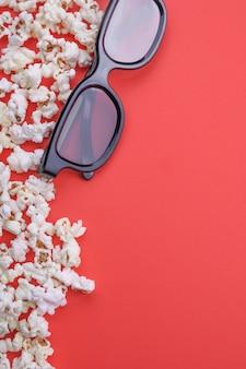 Óculos 3d e pipoca em um fundo vermelho. vista do topo.