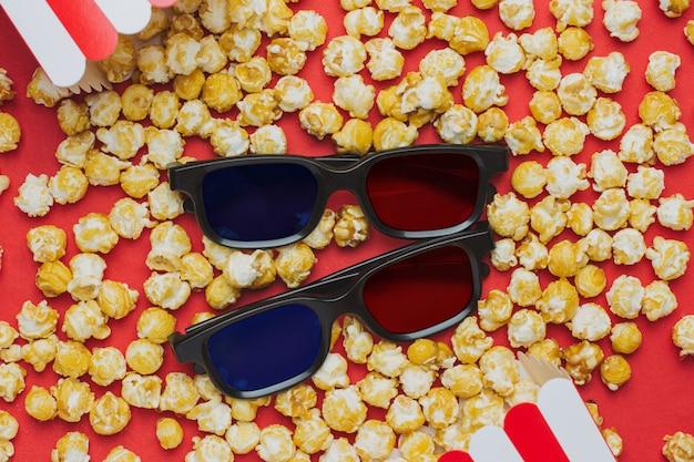 Óculos 3d e pipoca na vista superior vermelha