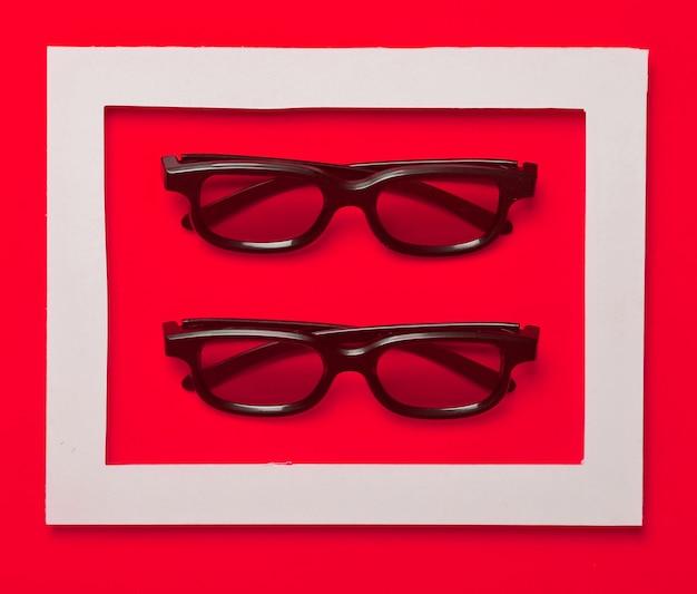 Óculos 3d em um quadro branco sobre um pastel amarelo.