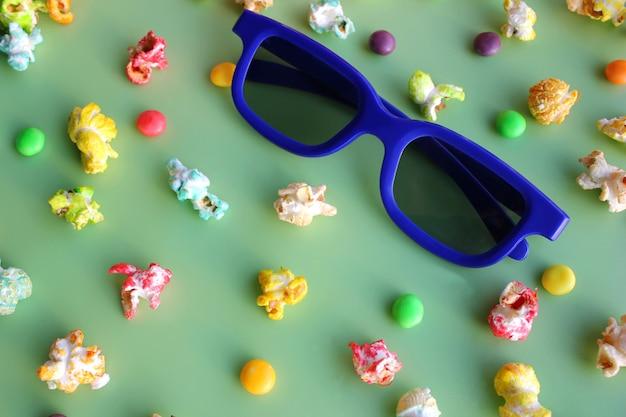 Óculos 3d para assistir filme e pipoca colorida sobre fundo verde.