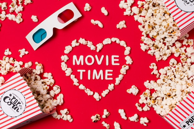 Óculos 3d; pipoca derramada da caixa com texto de tempo de filme em forma de coração no pano de fundo vermelho