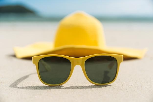 Óculos amarelos e chapéu na praia