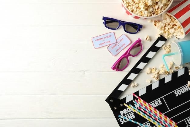Óculos, baldes com pipoca, bilhetes, claquete, bebida, sobre fundo branco de madeira