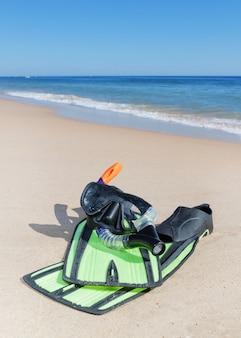 Óculos, barbatanas, snorkel na praia. perto da água.