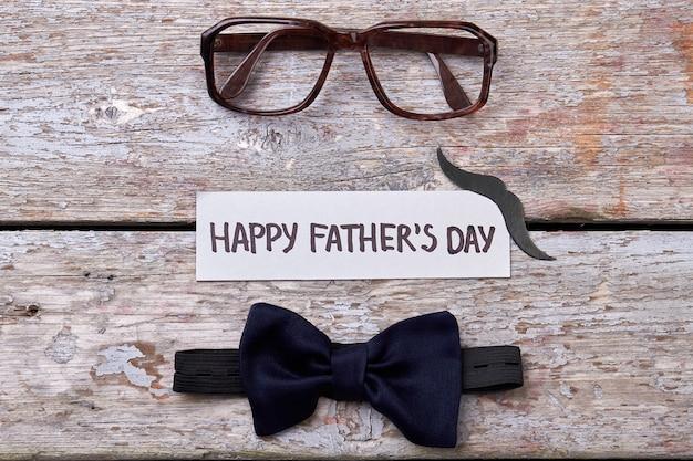 Óculos, bigode e gravata borboleta. óculos e cartão em madeira. moda do dia dos pais.